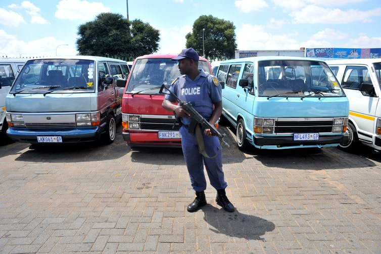 Policeman stands guard during a protest by minibus taxi operators