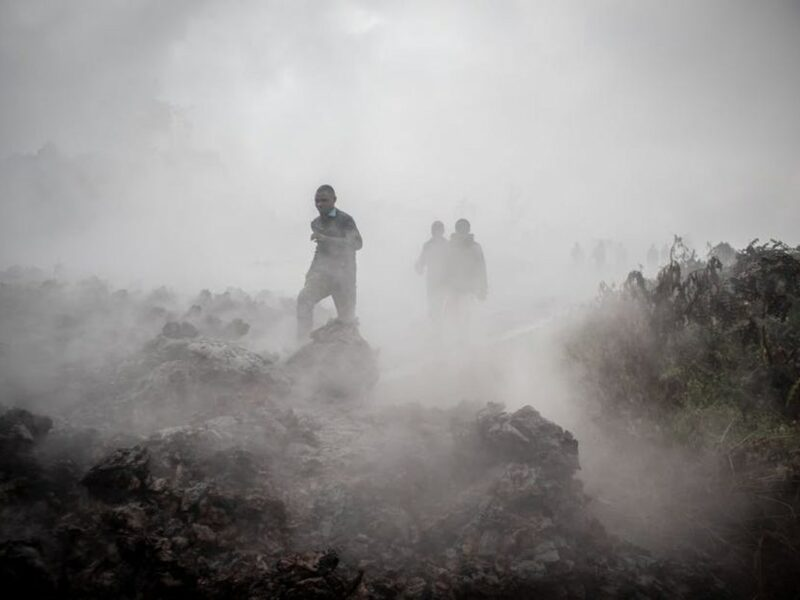 Men cross the front of the still smoking lava rocks from an eruption of the Mount Nyiragongo on May 23, 2021 in Goma in the east of the Democratic Republic of Congo. GUERCHOM NDEBO/AFP via Getty Images.